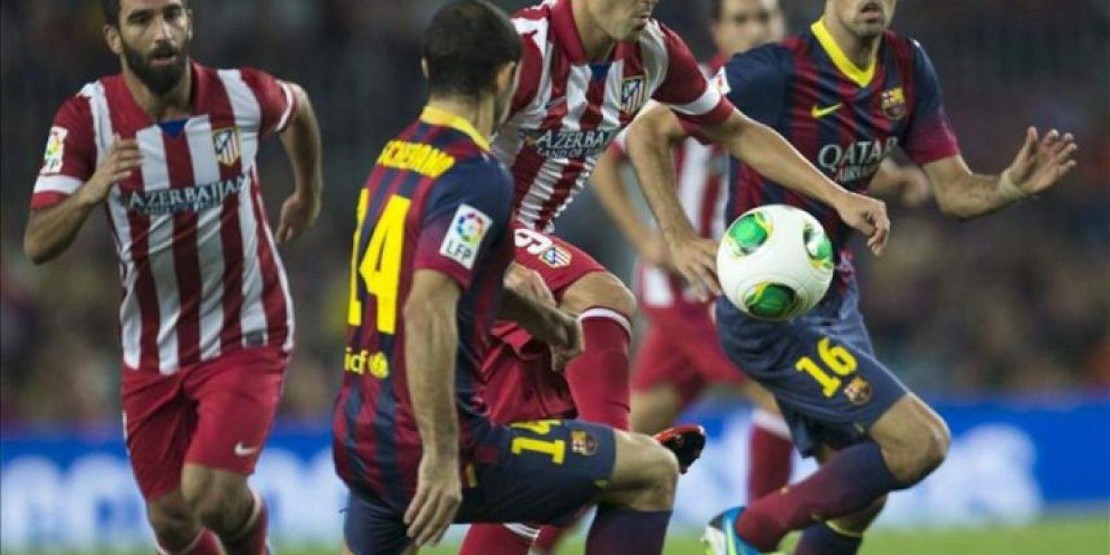 El defensa argentino del FC Barcelona, Javier Mascherano (2i), lucha el balón con David Villa (2d), del Atlético de Madrid, durante el partido de vuelta de la Supercopa de España que los dos equipos disputaron en el Camp Nou, en Barcelona. EFE