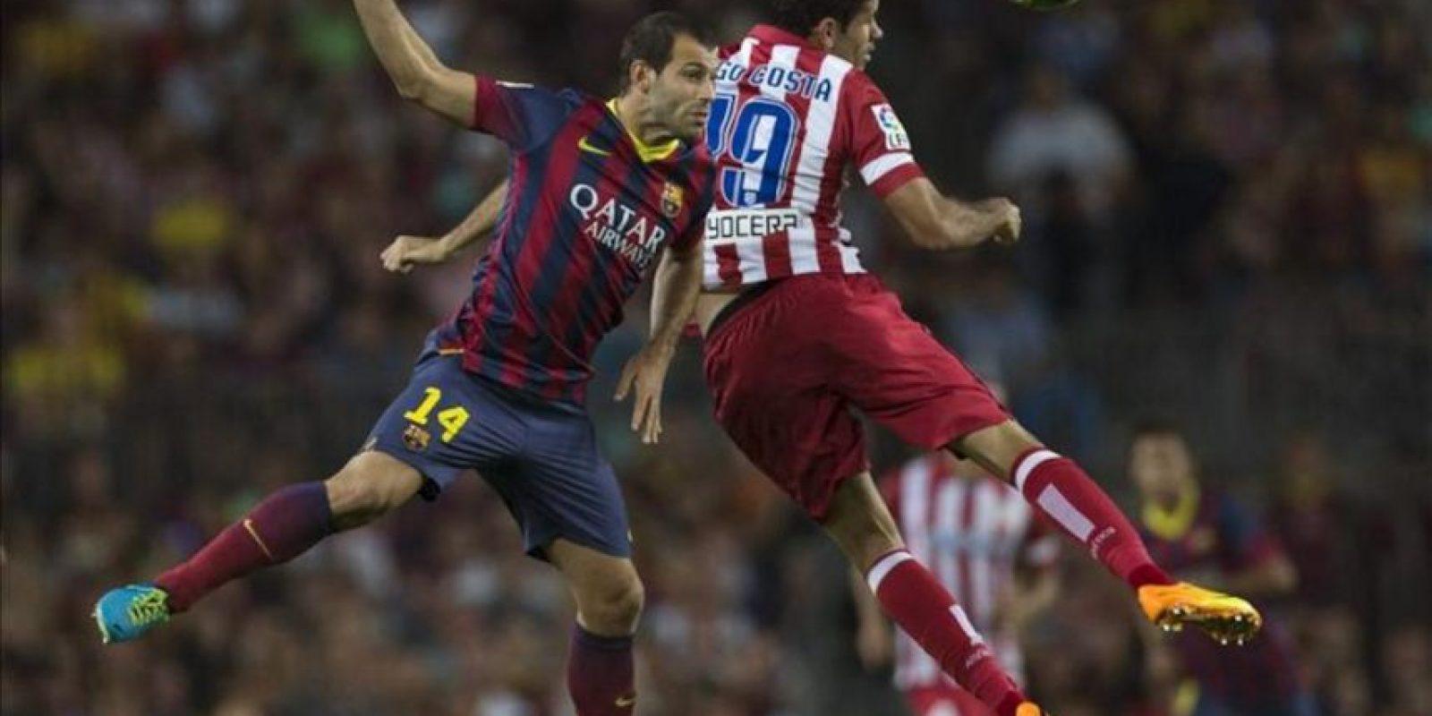 El defensa argentino del FC Barcelona, Javier Mascherano (i), salta por el balón con el brasileño Diego Costa, del Atlético de Madrid, durante el partido de vuelta de la Supercopa de España que los dos equipos disputaron en el Camp Nou, en Barcelona. EFE