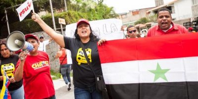 Un grupo de personas, seguidores del Gobierno de Venezuela, manifiesta su rechazo a una posible intervención militar de potencias extranjeras en Siria, frente a la embajada de ese país, en Caracas (Venezuela). EFE