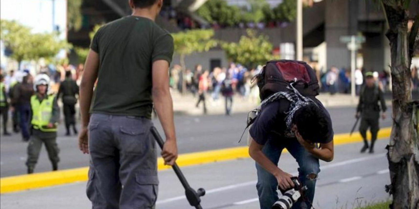 El fotógrafo de Agencia Efe Luis Eduardo Noriega (d) recibe un golpe de un policía vestido de civil (i) el 29 de agosto de 2013, en Medellín (Colombia). EFE