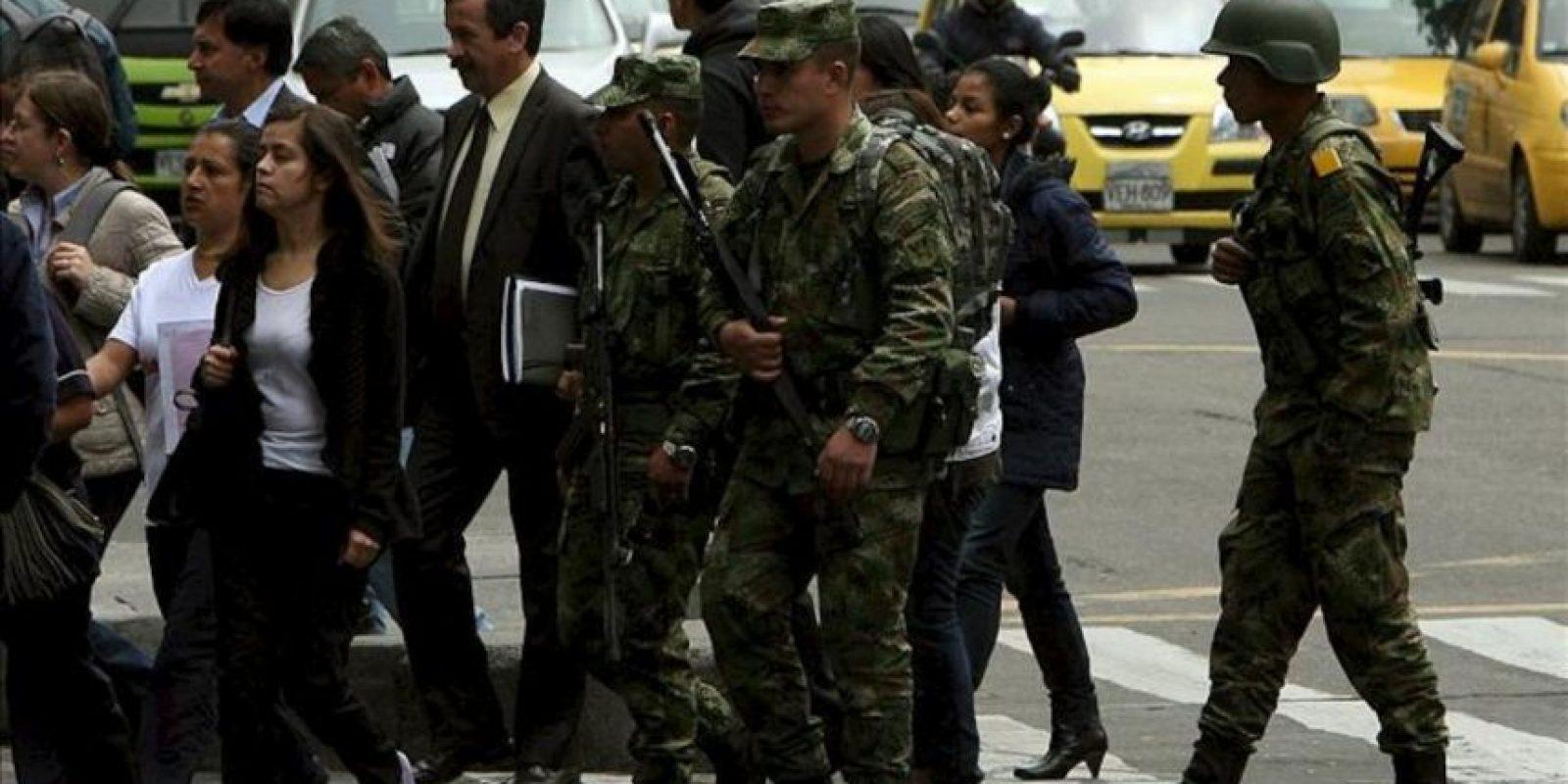 Personas y militares caminan en Bogotá (Colombia). El presidente de Colombia, Juan Manuel Santos, anunció que ordenó la militarización de la capital colombiana para garantizar la seguridad ciudadana, tras los disturbios del jueves que dejaron dos muertos, más de un centenar de heridos y daños a locales comerciales en la capital. EFE