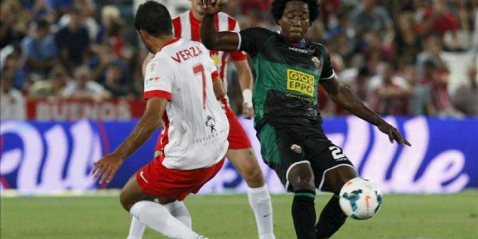 El centrocampista de la UD Almería, Verza (i), lucha el balón con Carlos Sánchez, del Elche CF, durante el partido, correspondiente a la tercera jornada de Liga en Primera División, que los dos equipos disputaron en el estadio de los Juegos Mediterráneos, en Almería. EFE