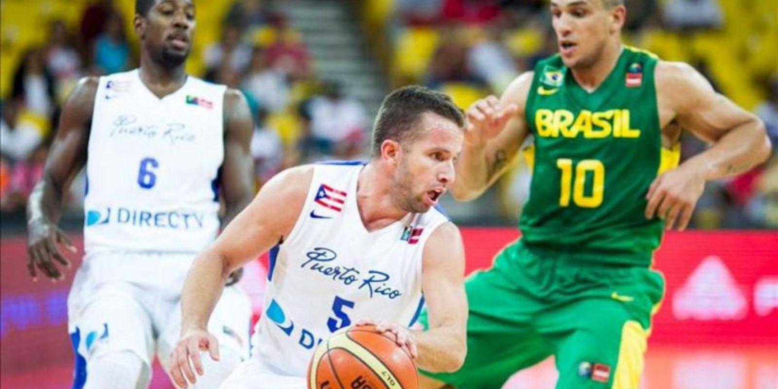 El jugador José Barea (c) de Puerto Rico controla el balón contra su oponente de Brasil (d), durante la primera jornada del Premundial de las Américas de Baloncesto que se disputa en Caracas (Venezuela). EFE