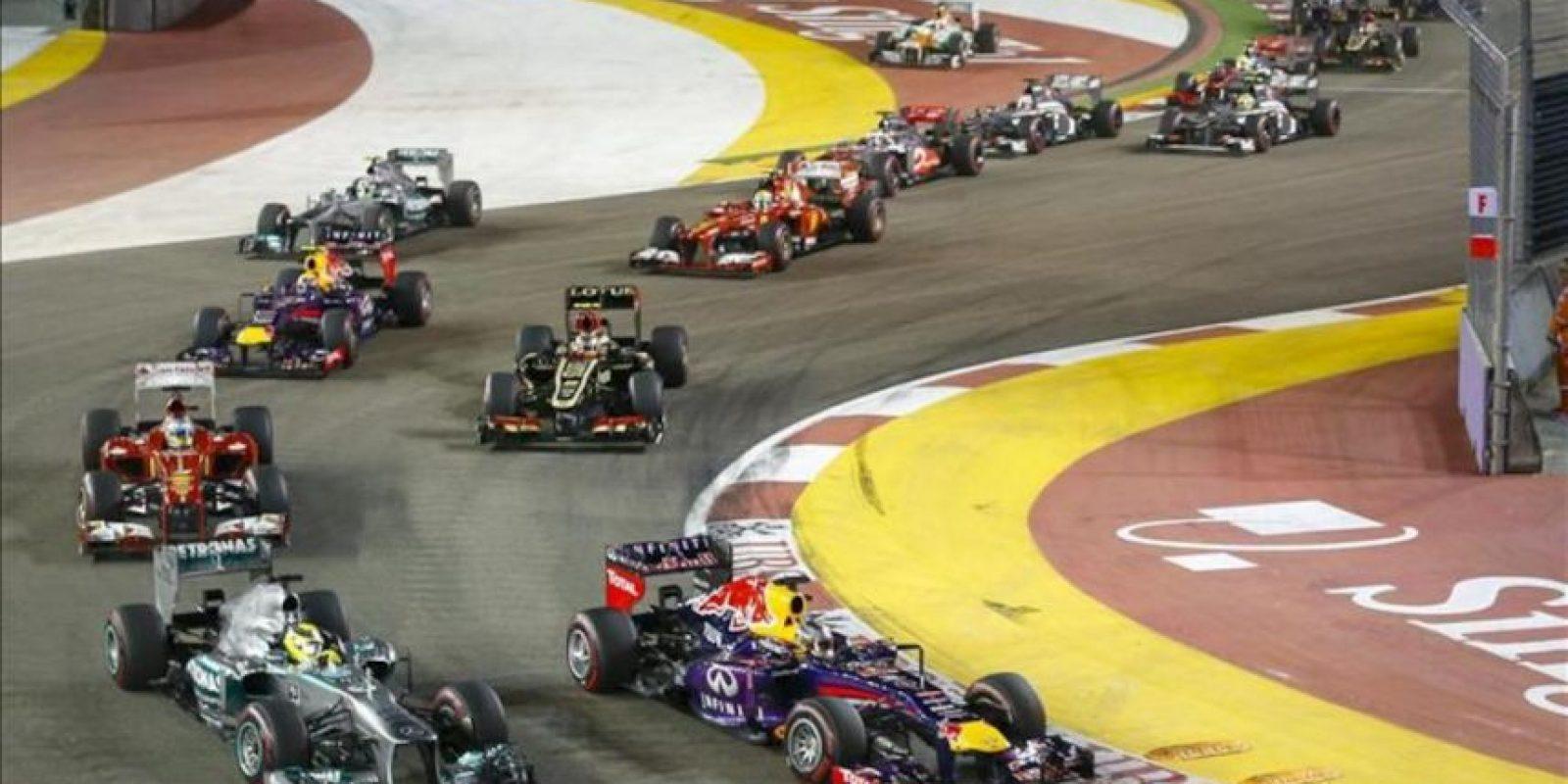 El piloto alemán de Fórmula Uno del equpo Red Bull Sebastian Vettel (d) sale primero y su compatriota Nico Rosberg, del equipo Mercedes AMG, trata de adelantarde en el GP de Singapur. EFE