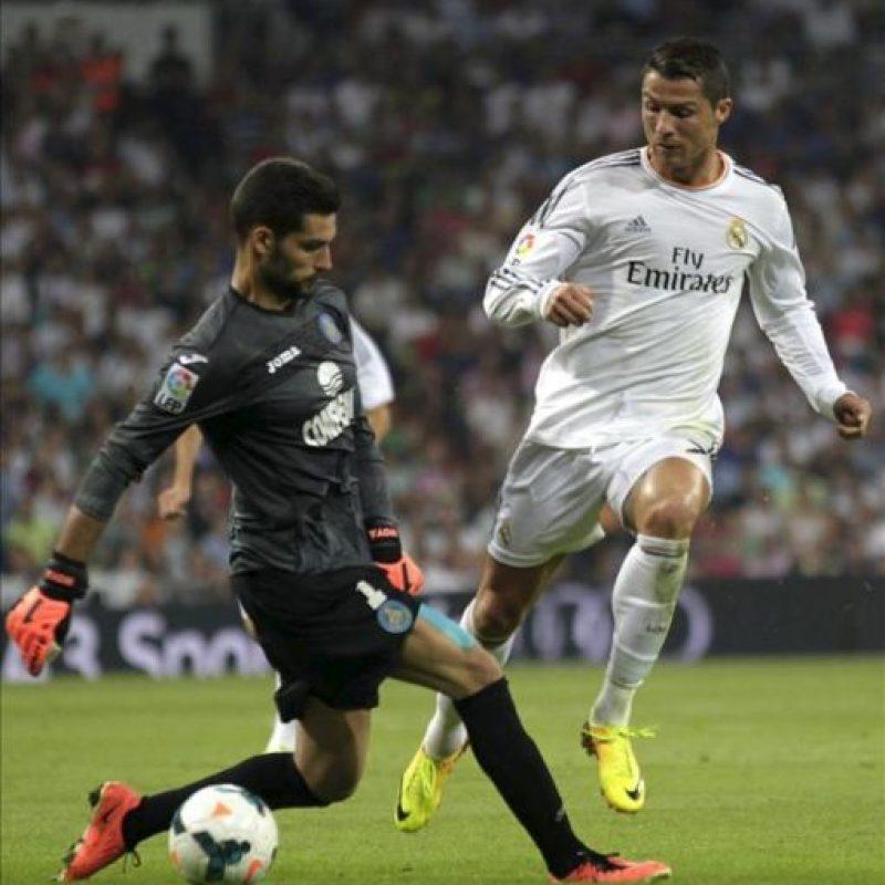 El delantero portugués del Real Madrid Cristiano Ronaldo (d) intenta superar a Miguel Moyá, portero del Getafe CF, durante el partido correspondiente a la quinta jornada de Liga que se disputó en el estadio Santiago Bernabéu, en Madrid. EFE
