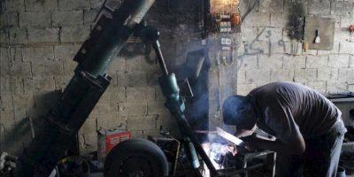 Un integrante de las tropas opositoras al régimen de Bachar al Asad, durante el proceso de fabricación de bombas y la reparación de artillería en el barrio de Tareq Al-Bab (Alepo). EFE
