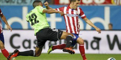 El delantero del Atlético de Madrid David Villa (d) trata de superar la defensa del francés Loties, de Osasuna, durante el partido de Primera División que disputaron en el estadio Vicente Calderón, en Madrid. EFE