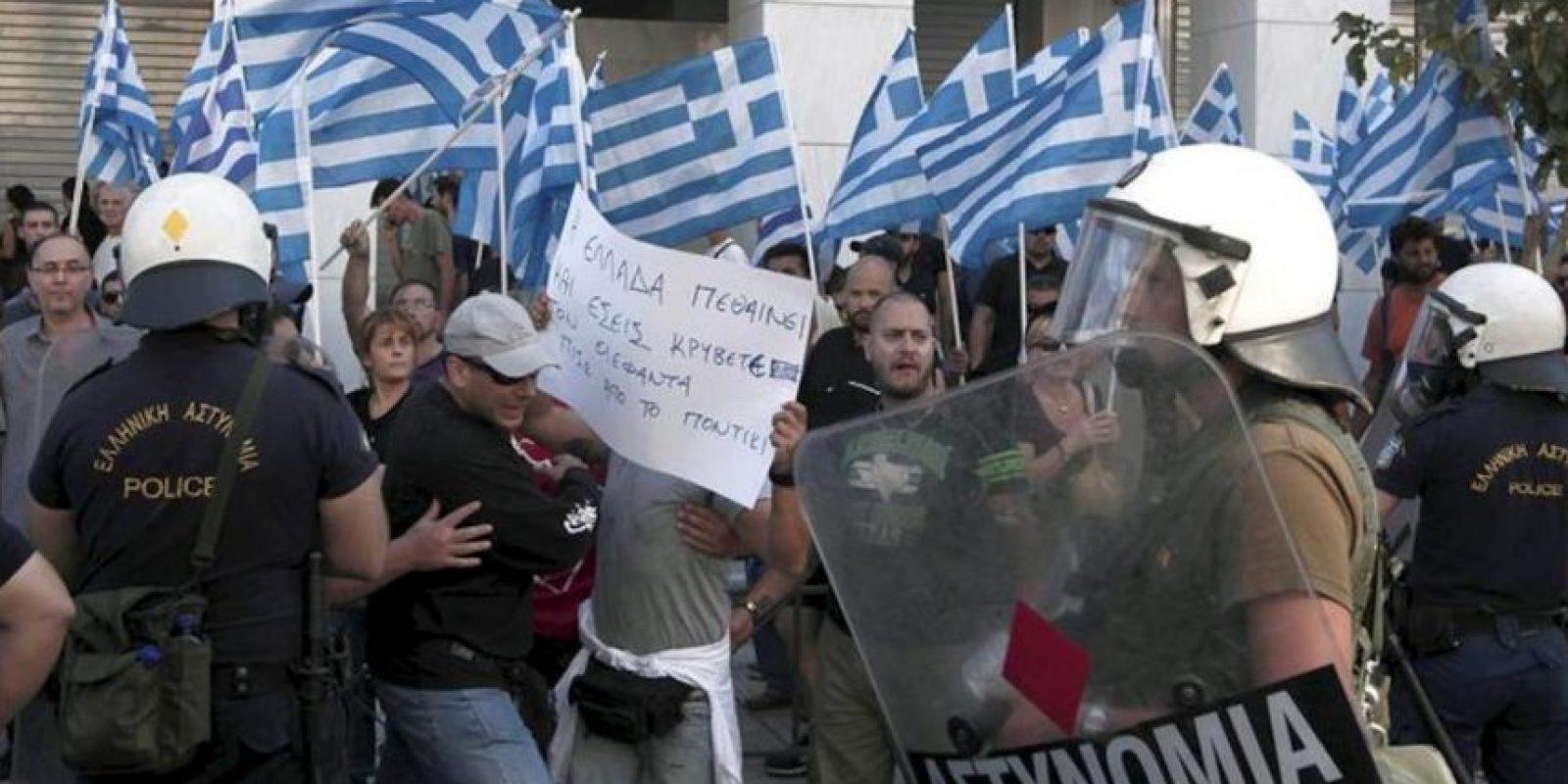 Policías antidisturbios tratan de contener los partidarios de la extrema derecha, ala del partido Amanecer Dorado, que se congregaron frente a la sede de la Policía de Atenas con banderas griegas para protestar por la detención del líder de su partido y de varios de sus dirigentes. EFE