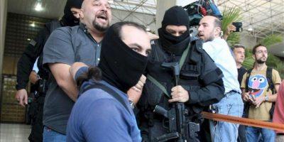 El diputado del partido ultra-derechista Amanecer Dorado, Ilias Panagiotaros (c), grita a los periodistas mientras es escoltado por policías enmascarados en la sede de la Policía de Atenas en Atenas, Grecia. EFE