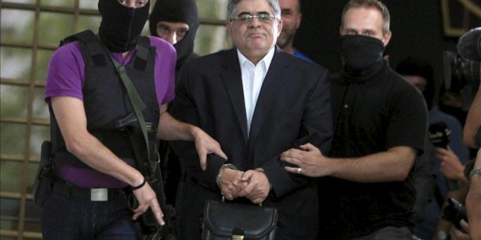 El lider del partido partido ultra-derechista griego Amanecer Dorado, Nikos Michaloliakos (c), es escoltado por policías fuera de la Jefatura de Policía de Atenas, en Atenas. EFE