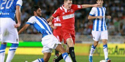 El delantero francés del Sevilla Kevin Gameiro (2-d) trata de escapar del mexicano Carlos Vela (2-i), de la Real Sociedad, durante el partido correspondiente a la séptima jornada de Liga en Primera División jugado en el estadio de Anoeta, en San Sebastián. EFE