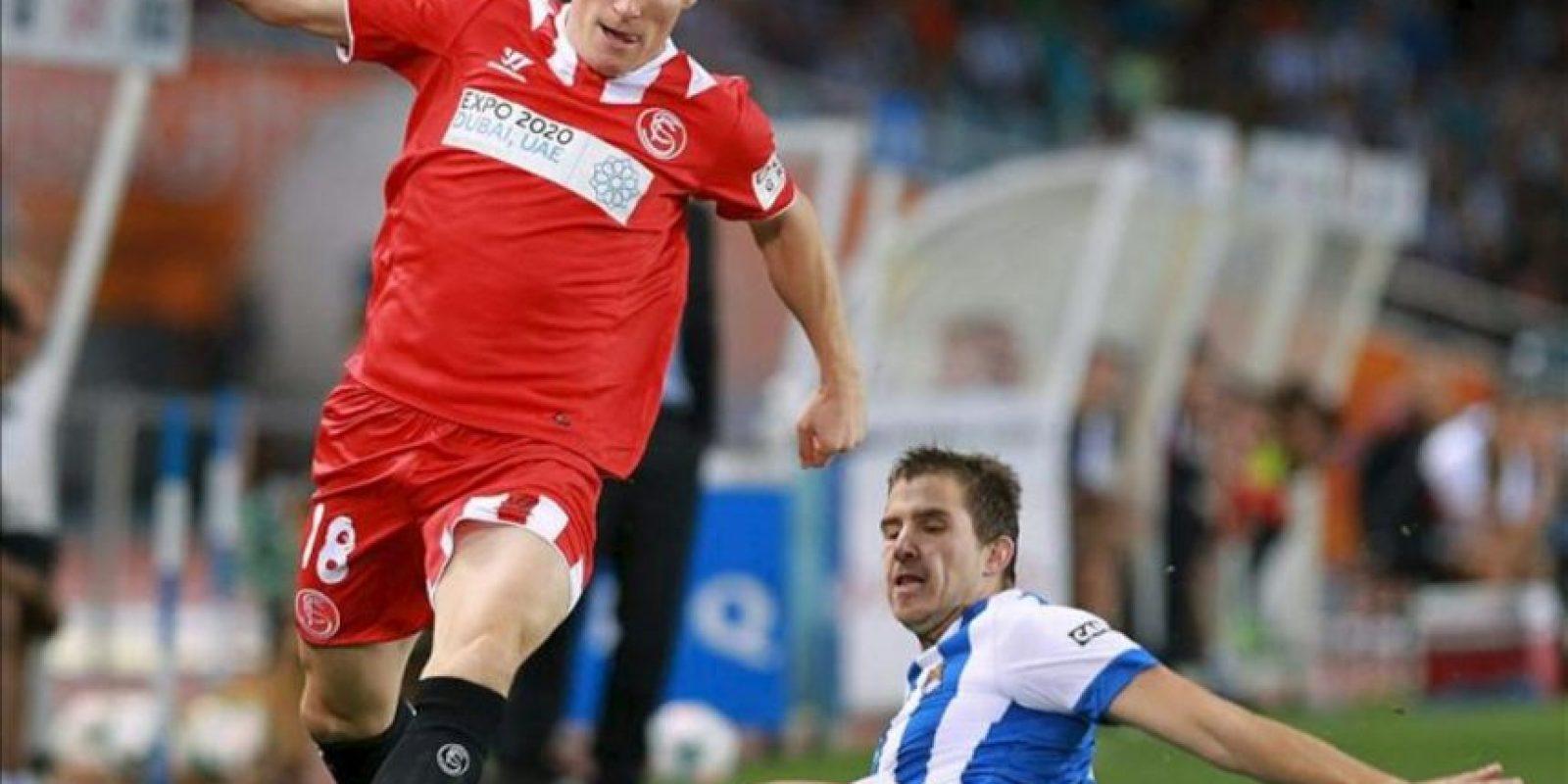 El delantero francés del Sevilla Kevin Gameiro (i) trata de escapar de Íñigo Martínez, de la Real Sociedad, durante el partido correspondiente a la séptima jornada de Liga en Primera División jugado en el estadio de Anoeta, en San Sebastián. EFE