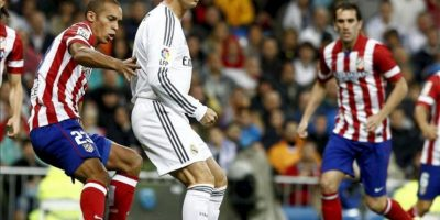 El delantero portugués del Real Madrid Cristiano Ronaldo (c) ante el defensa brasileño del Atlético de Madrid João Miranda (i) durante el partido de la séptima jornada de Liga de Primera División, disputado en el estadio Santiago Bernabéu. EFE