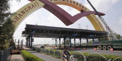"""Una mujer en bicicleta pasa junto a un arco que señala la """"Zona de libre comercio de Shanghái"""", en China. EFE"""