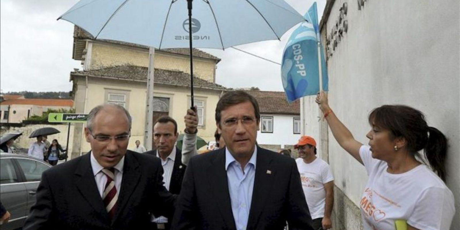 El primer ministro portugués y líder del Partido Socialdemócrata (PSD) luso, Pedro Passos Coelho (c), y el candidato del PSD para el ayuntamiento de Lamego, Francisco Lopes (i), asisten a un acto de campaña electoral, el pasado viernes. EFE
