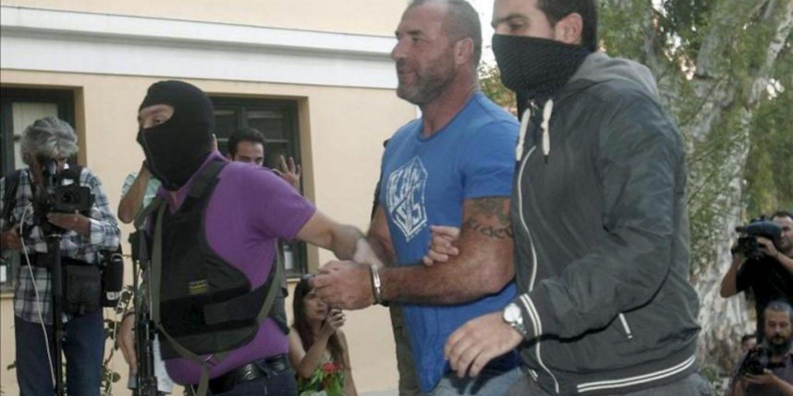 El diputado del ultra-derechista partido Amanecer Dorado Nikos Michos (C) es escoltado por policías enmascarados a la oficina del fiscal en Atenas, Grecia. EFE