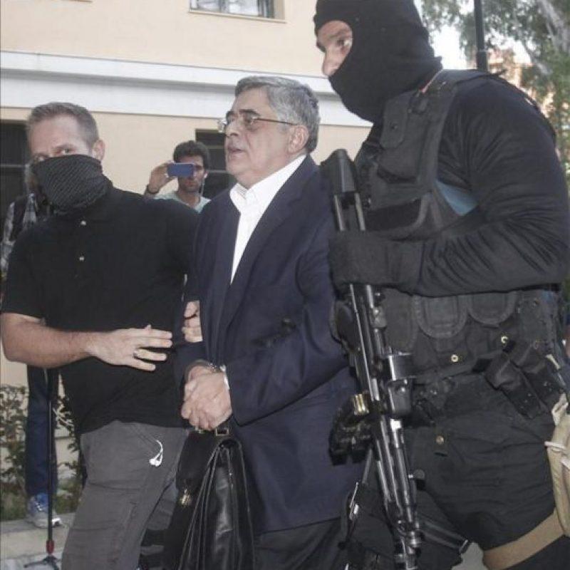 El líder del partido neonazi griego Amanecer Dorado, Nikos Michaloliakos (c) es escoltado por policías enmascarados a la oficina del fiscal en Atenas. EFE