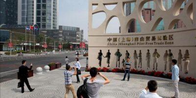 Varias personas toman fotografía de la entrada de la zona de libre comercio inaugurada hoy en Shanghai. EFE