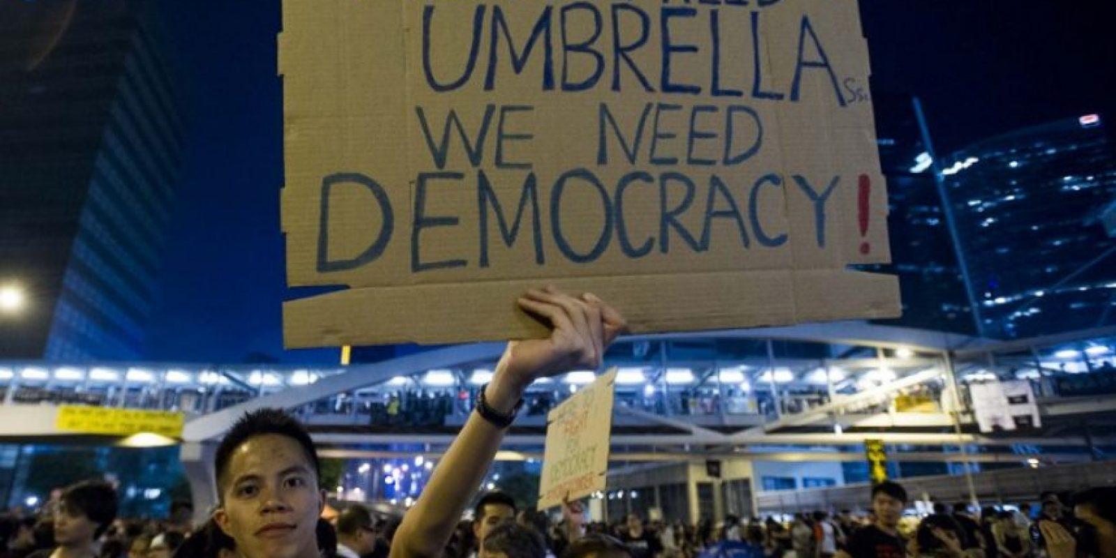 """En el cartel se lee """"No necesitamos sombrillas, necesitamos democracia"""" Foto:AFP"""