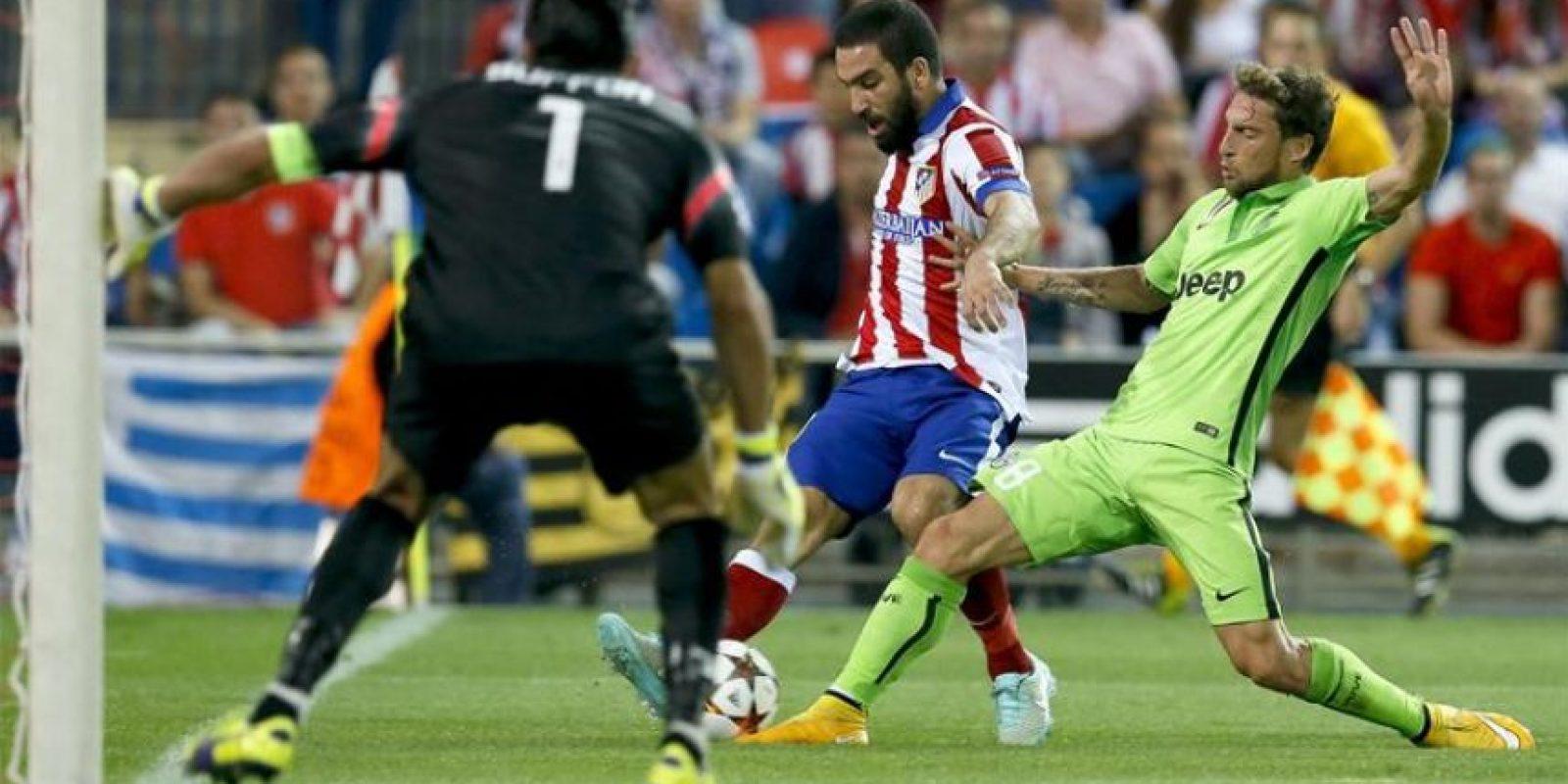 El centrocampista turco del Atlético de Madrid Arda Turan (c) con el balón ante el centrocampista del Juventus Claudio Marchisio (d) y el portero Gianluigi Buffon (i, de espaldas) durante el partido de la segunda jornada de la fase de grupos de la Liga de Campeones que Atlético de Madrid y Juventus disputaron en el estadio Vicente Calderón, en Madrid. EFE