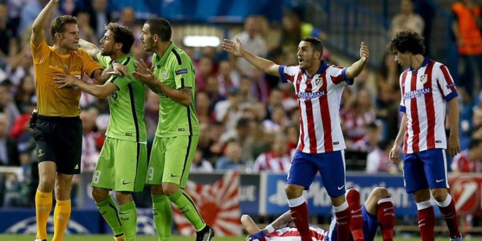 El árbitro Félix Brych saca cartulina amarilla a Leonardo Bonucci (3i), de la Juventus, durante el partido de la segunda jornada de la fase de grupos de la Liga de Campeones en el estadio Vicente Calderón, en Madrid. EFE
