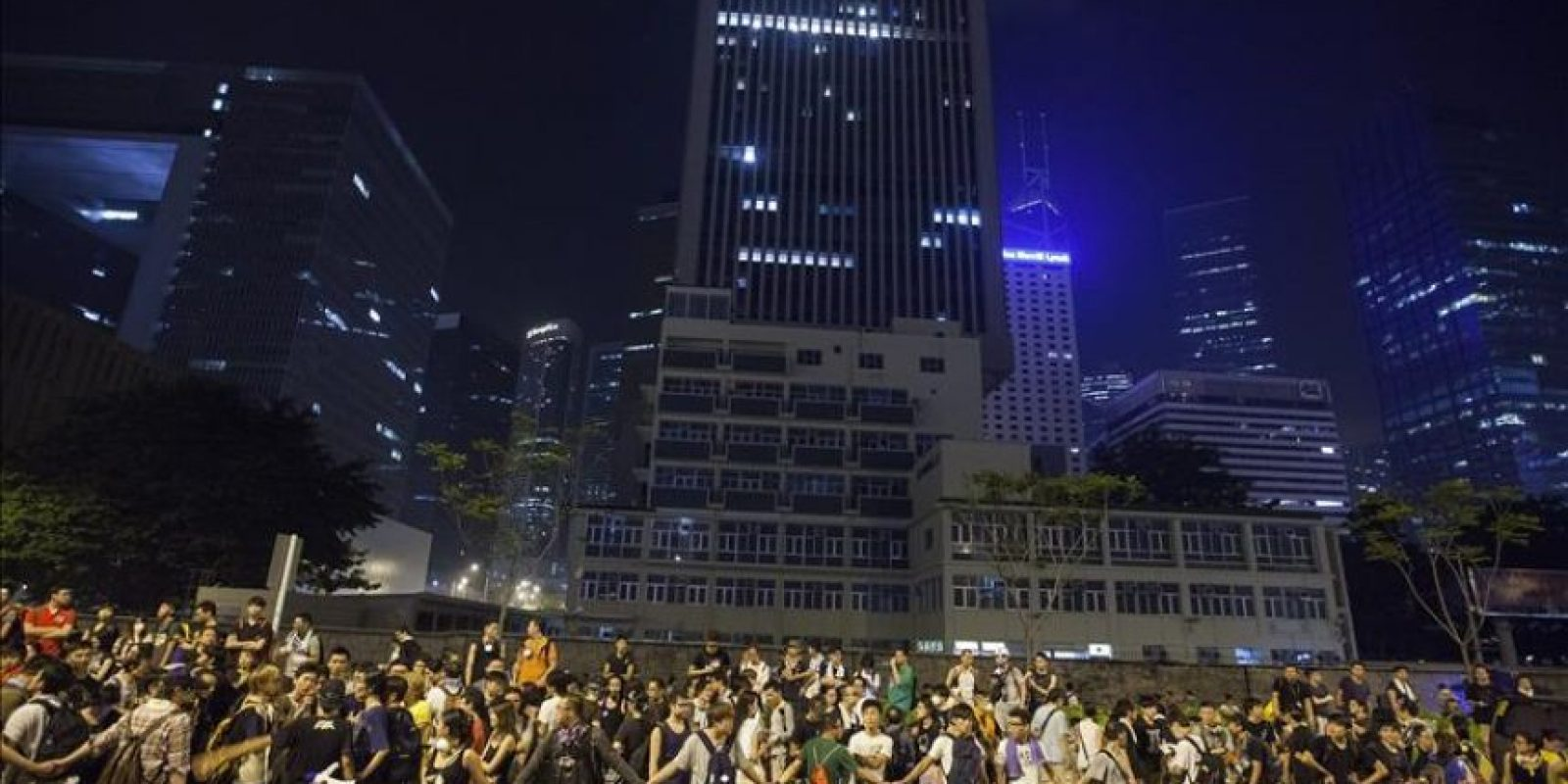 Manifestantes prodemocracia se cogen de las manos para mantener atrás a la multitud y conducir el tráfico, cerca de la oficina del jefe ejecutivo de Hong Kong, Cy Leung Chun-ying, en el quinto día de desobediencia civil en Hong Kong. EFE