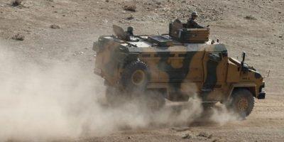 Soldados turcos vigilan la frontera de Sanliurfa, Turquía, hoy, junto a posiciones de las fuerzas del Estado Islámico en la localidad de Kobani, Siria.