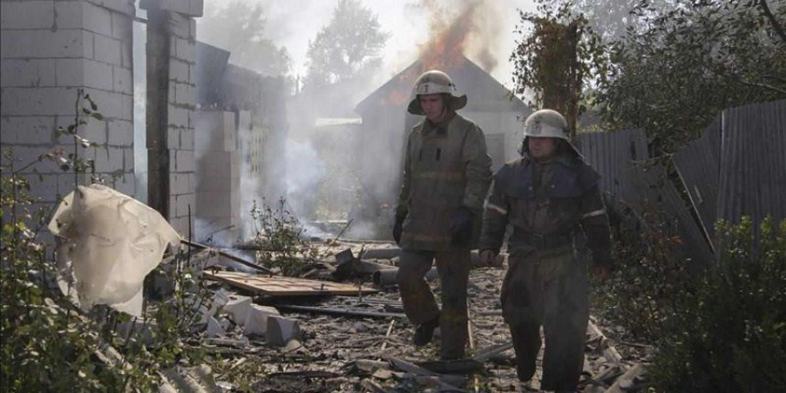 Dos bomberos trabajan en un edificio bombardeado cerca del aeropuerto de Donetsk, Ucrania, ayer. EFE
