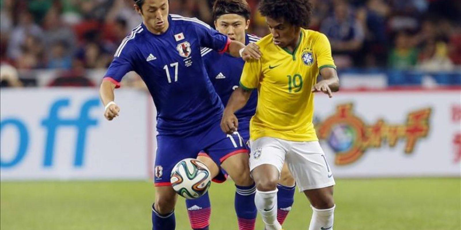 El delantero brasileño Willian (d) lucha por el balón con el japonés Ryota Morioka (i) durante el amistoso de ambas selecciones disputado en el estadio nacional de Singapur, Singapur hoy 14 de octubre de 2014. EFE