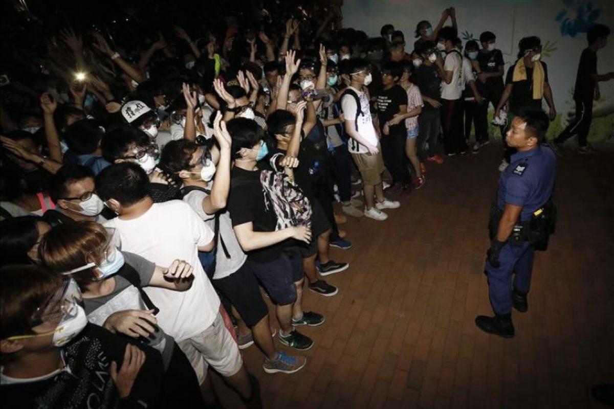 Un policía de Hong Kong (d) se enfrenta a manifestantes del movimiento Occupy Central, quienes bloquean el acceso al Distrito Admiralty de Hong Kong (China) este jueves. EFE