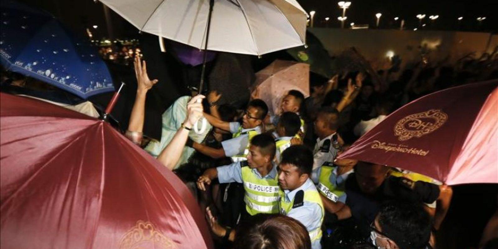 Policías de Hong Kong (c) intentan hacer retroceder a manifestantes del movimiento Occupy Central, quienes bloquean el acceso al Distrito Admiralty de Hong Kong (China) este jueves, en su decimoctavo día de protestas. EFE