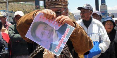 """Un sacerdotes aimara sostiene una imagen del exministro de Defensa de Bolivia, Carlos Sánchez Berzaín, durante un mitin junto con mineros bolivianos y familiares de los fallecidos y heridos del conocido """"Octubre negro"""" este 17 de octubre de 2014, en la ciudad de El Alto, vecina de La Paz (Bolivia). EFE"""