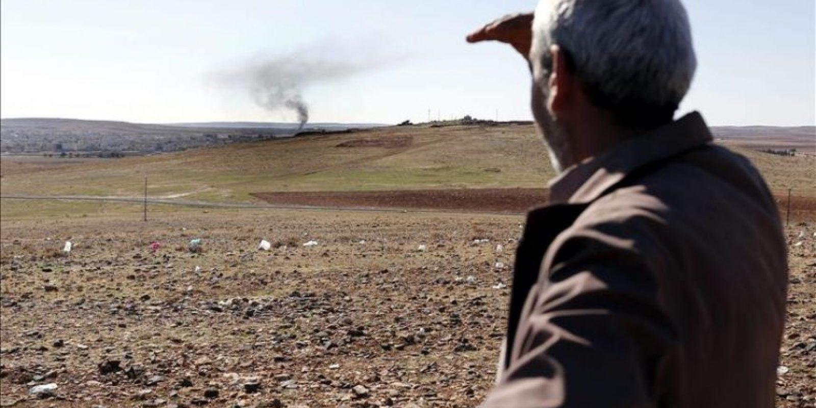 Un hombre observa una columna de humo que se eleva en la localidad kurdo-siria de Kobani vista desde la frontera en Sanlirufa (Turquía) tras un supuesto ataque aéreo de Estados Unidos este martes. EFE