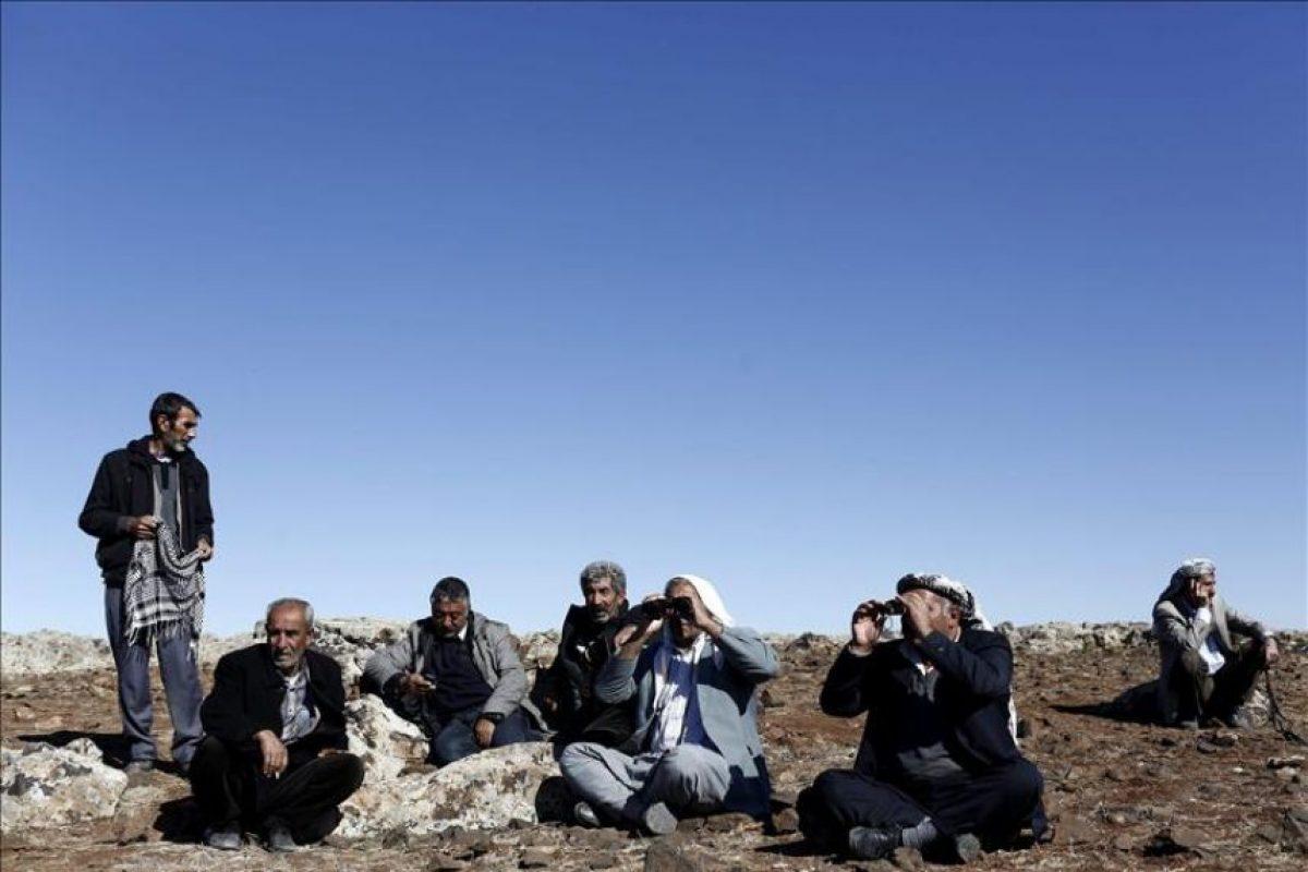 Un grupo de hombres observa una columna de humo se eleva en la localidad kurdo-siria de Kobani vista desde la frontera en Sanlirufa (Turquía) tras un supuesto ataque aéreo de Estados Unidos este martes. EFE