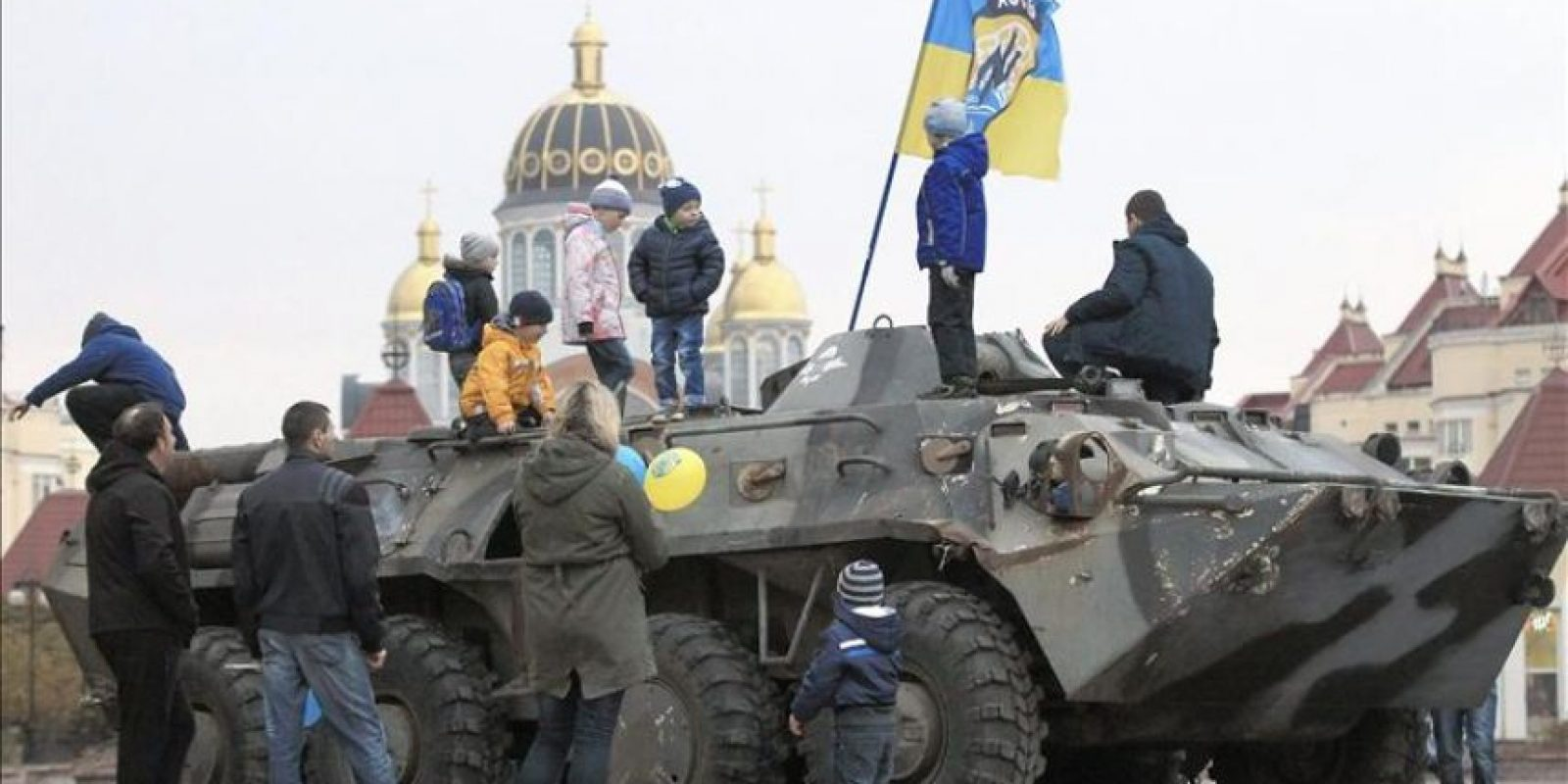 Varios niños juegan con unos tanques interceptados por el ejército ucraniano a las fuerzas rebeldes del battallón de Azov, en Kiev. EFE