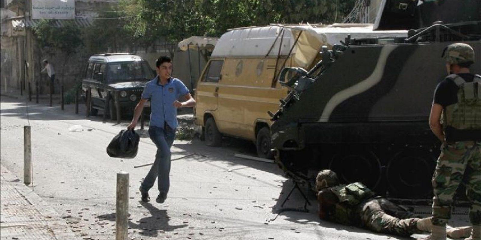 Dos soldados se protegen detrás de un vehículo armado, hoy en la localidad de Trípoli. EFE