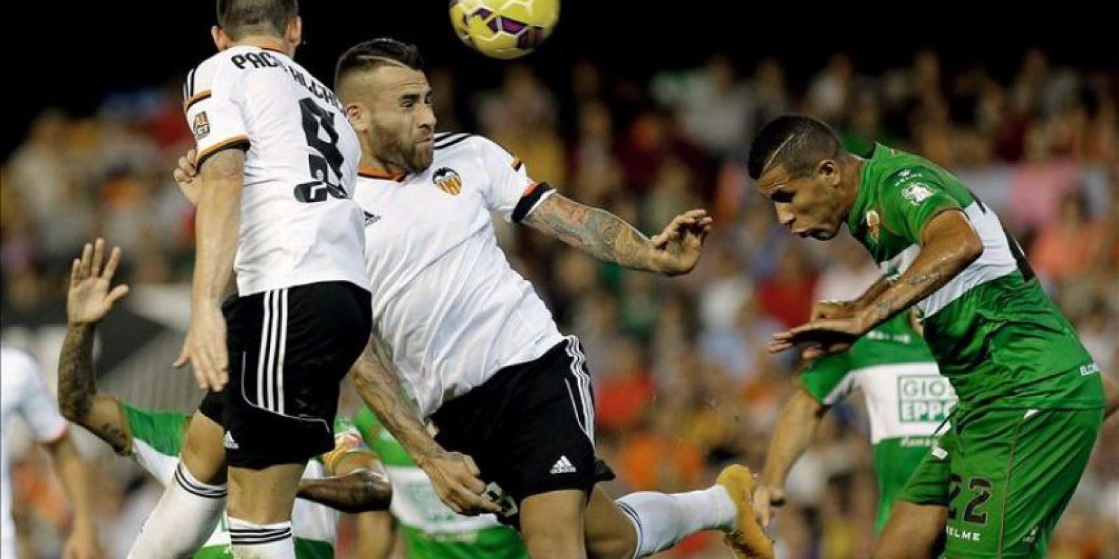 El defensa argentino del Valencia, Nicolás Otamendi (2i), despeja un balón ante el delantero brasileño del Elche, Jonathas, durante el encuentro correspondiente a la novena jornada de primera división. EFE