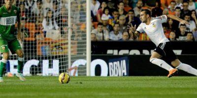 El delantero del Valencia Paco Alcácer (d) con el balón ante el defensa chileno del Elche Enzo Roco (i), durante el partido de la novena jornada de Liga de Primera División disputado en el estadio de Mestalla. EFE