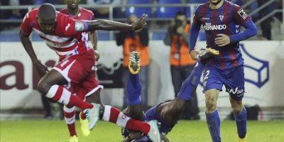 El centrocampista del Eibar, Derek Boateng (suelo), cae ante el delantero nigeriano del Granada, Isaac Ajayi, durante el encuentro correspondiente a la novena jornada de primera división, que han disputado esta noche en el estadio de Ipurúa. EFE
