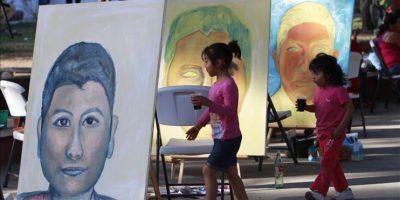 Jóvenes artistas independientes que apoyan a los 43 normalistas desaparecidos plasman en lienzo, este 26 de octubre, la imagen de cada uno de los estudiantes en la plaza principal de Chilpancingo, México. EFE