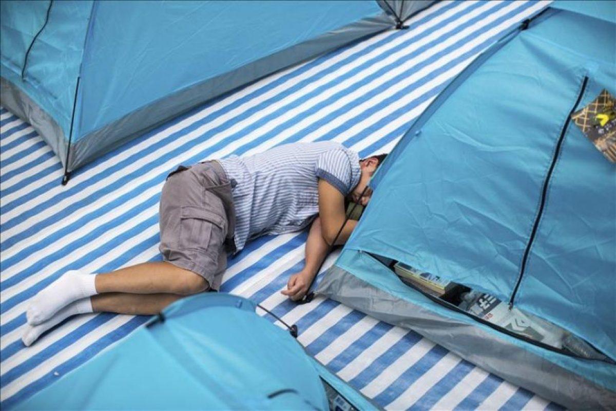 Un hombre descansa junto a varias tiendas de campaña en la calle Nathan cortada por manifestantes mientras continúan las protestas en Hong Kong (China). EFE