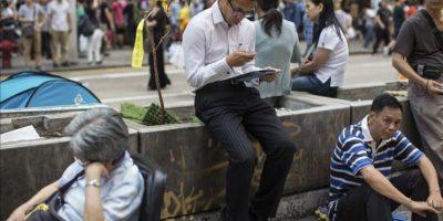 Varias personas permanecen en la calle Nathan cortada por manifestantes mientras continúan las protestas en Hong Kong (China). EFE