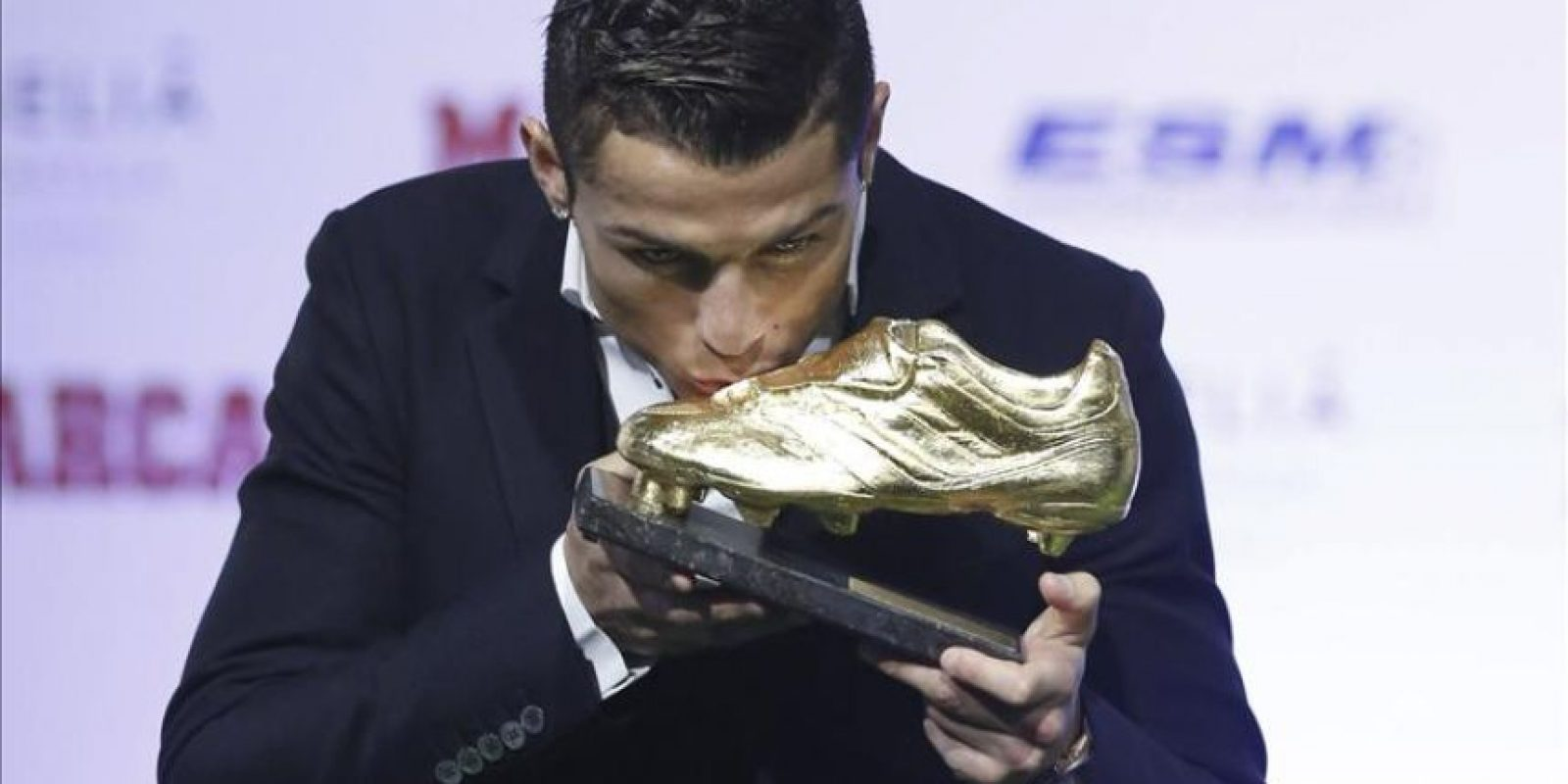 El delantero portugués del Real Madrid, Cristiano Ronaldo, besa la Bota de Oro 2013-2014, tras recibir el trofeo de manos del presidente del club, Florentino Pérez. EFE