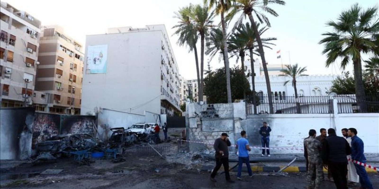 Miembros de los servicios de seguridad inspeccionan la escena tras la explosión hoy de dos coches cerca de la Embajada de Egipto en Trípoli (Libia). Dos coches bomba estallaron esta madrugada en Trípoli cerca de las embajadas de Egipto y Emiratos Árabes Unidos sin causar víctimas mortales, informaron a Efe fuentes de seguridad de la capital libia. EFE