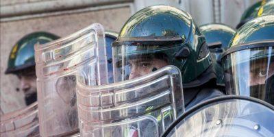 Agentes de policía italianos, se protegen mientras varios manisfestantes lanzan huevos y dispositivos pirotécnicos durante una protesta ante el Ministerio de Economía en Roma, Italia, hoy. EFE
