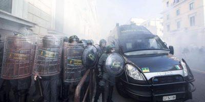 Agentes de policía italianos, se protegen mientras varios manisfestantes lanzan huevos y dispositivos pirotécnicos durante una protesta ante el Ministerio de Economía en Roma, Italia, hoy.