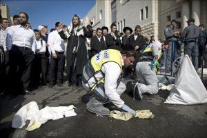 Personal del servicio de emergencias limpia las manchas de sangre tras el ataque contra una sinagoga en Jerusalén (Israel). EFE