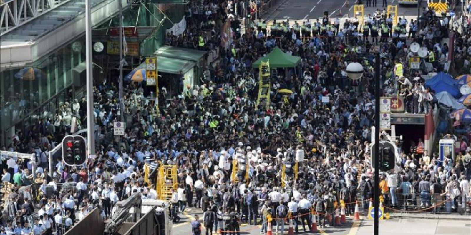 Trabajadores retiran barricadas ante la multitud en el distrito de Mong Kok en Hong Kong (China). EFE