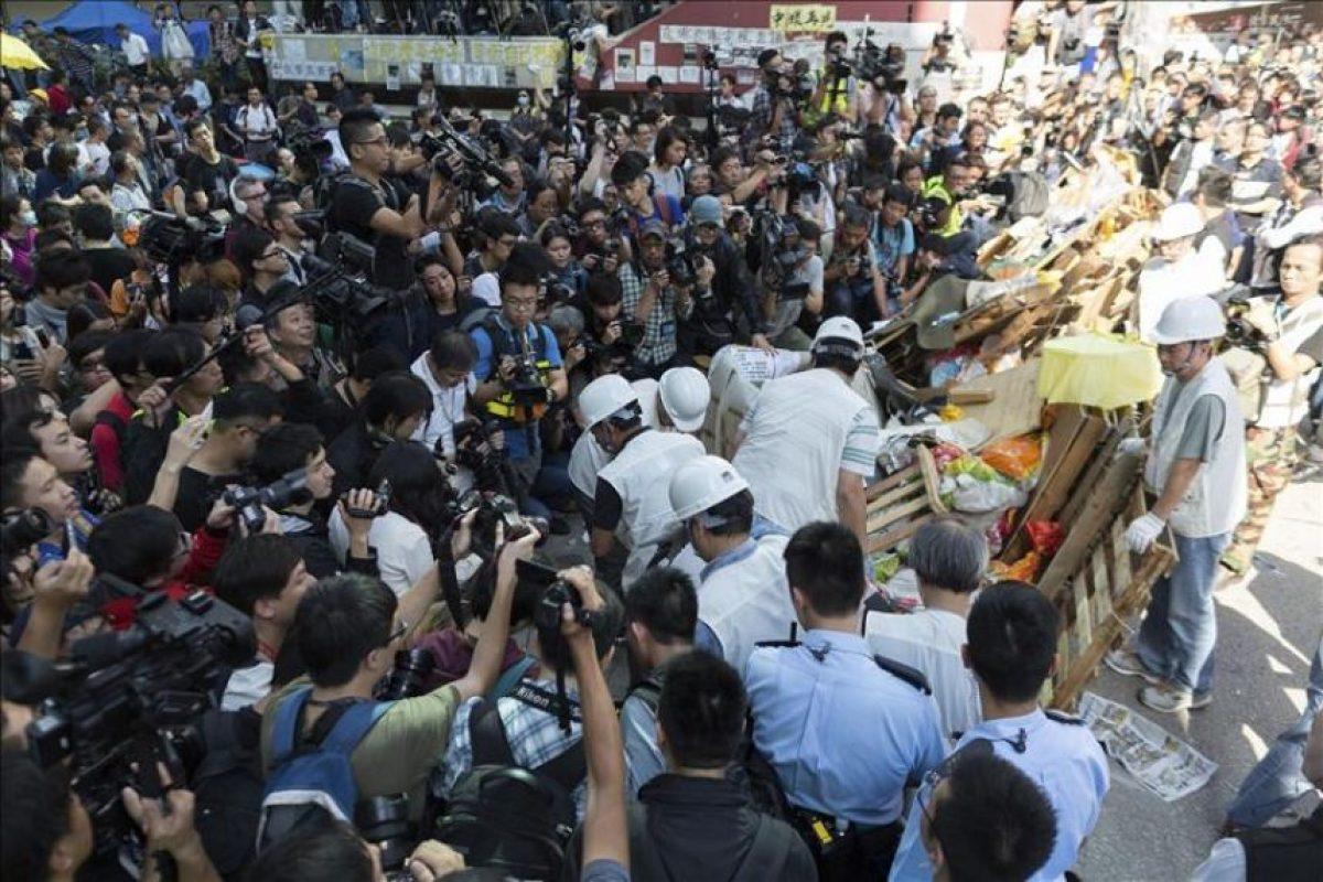 Trabajadores (con chalecos blancos) retiran las barricadas de una parte de la calle Argyle en el distrito de Mong Kok en Hong Kong (China). EFE