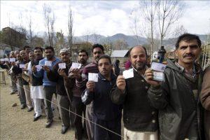 Varios votantes muestran sus carnés de identidad mientras aguardan ante un colegio electoral para participar en la jornada inaugural de las elecciones de la Cachemira india en Bhadarwah, a unos 210 kilómetros de Jammu, la capital de invierno de Cachemira (India). EFE